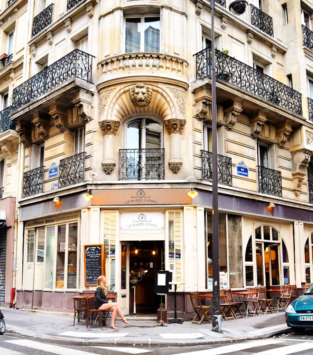Girl sitting on chair and table out the front of Paris restaurant