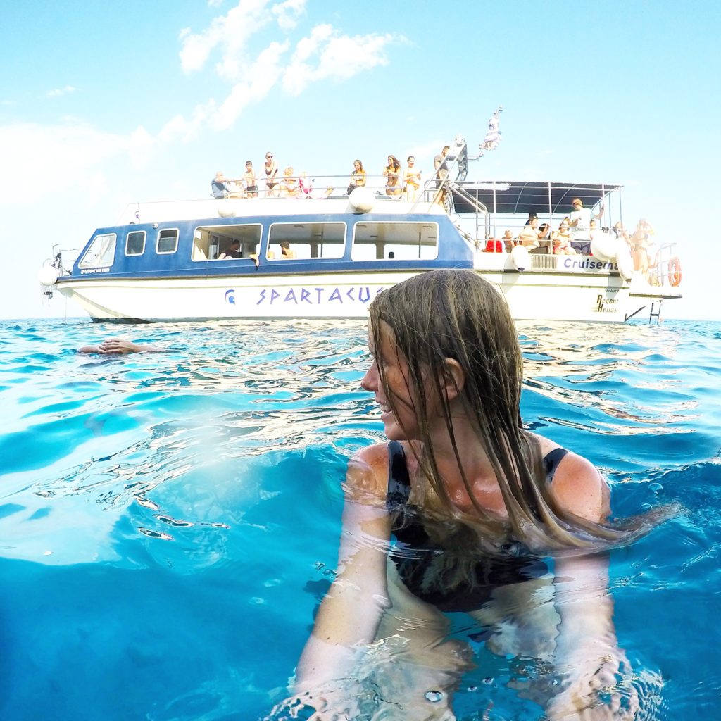 Girl swimming next to boat in Zante