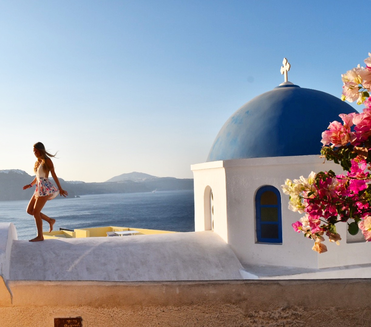 Sarah Latham running across blue domed churches in Oia Santorini at Sunrise