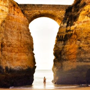 Sarah Latham standing on the beach at the ocean underneath bridge arch between two cliffs in Lagos, Portugal