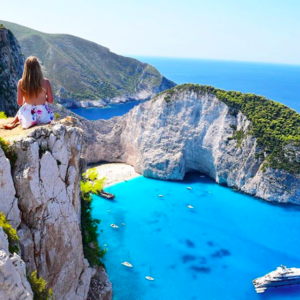 Girl sitting on cliffside at Navagio Beach in Zakinthos