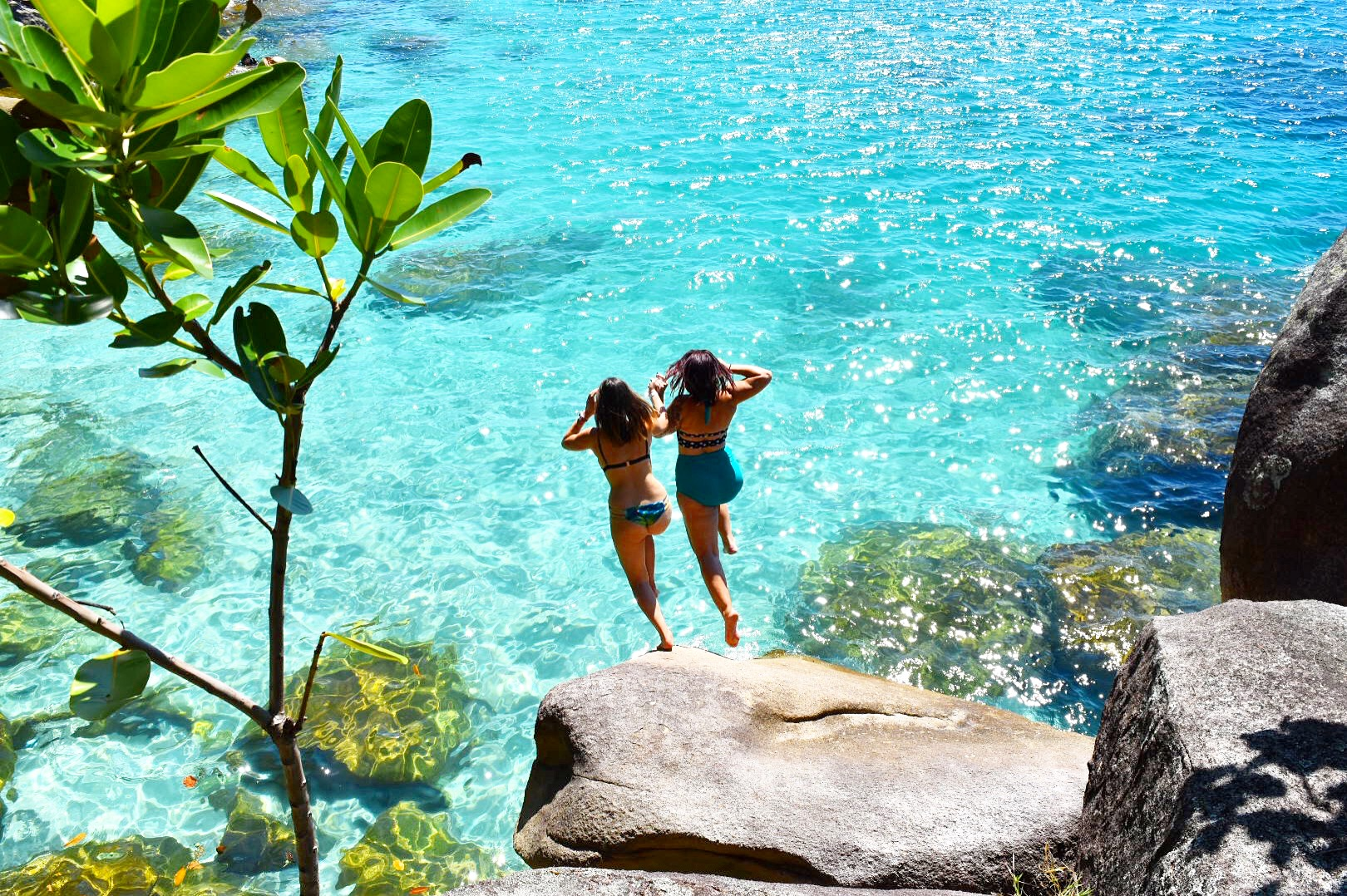 Two girls jumping into water at Nudey Beach Fitzroy Island