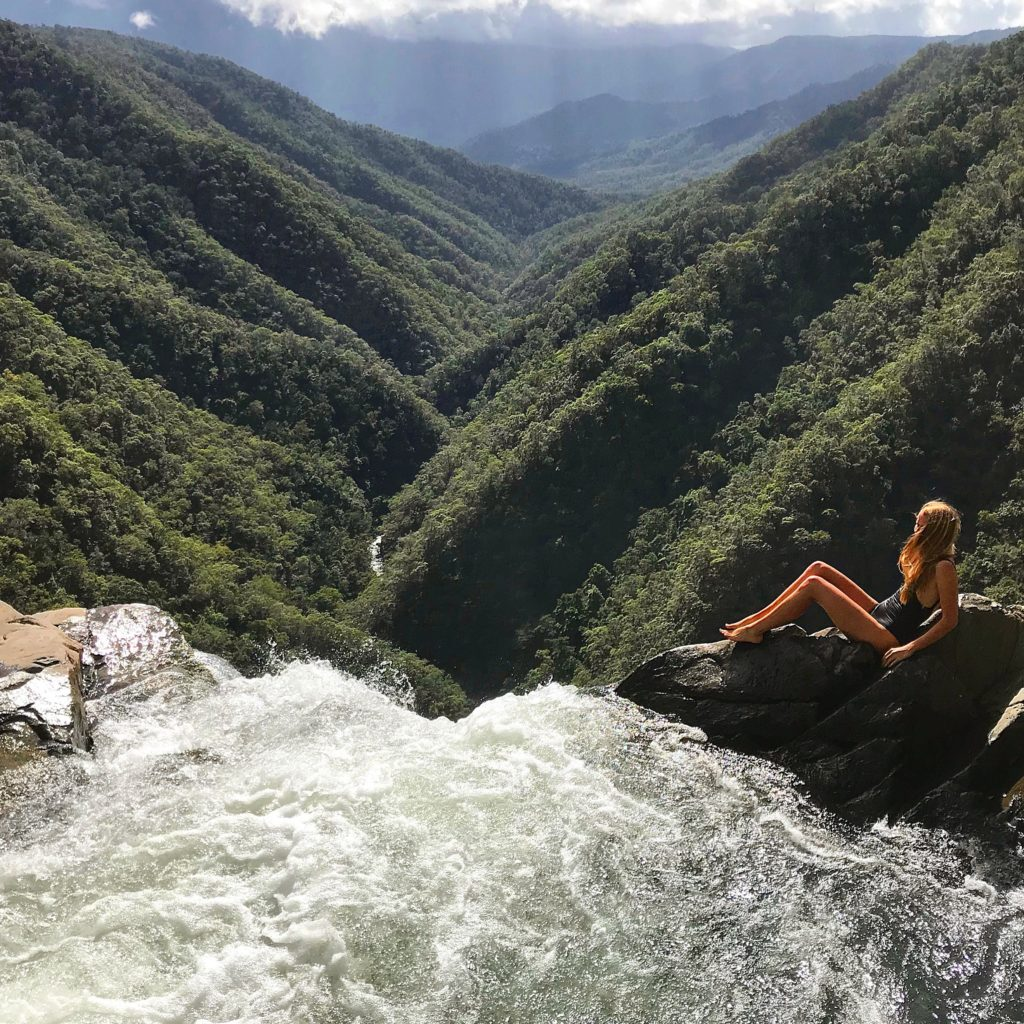 Girl sitting on edge of top of Windin Falls overlooking valley below