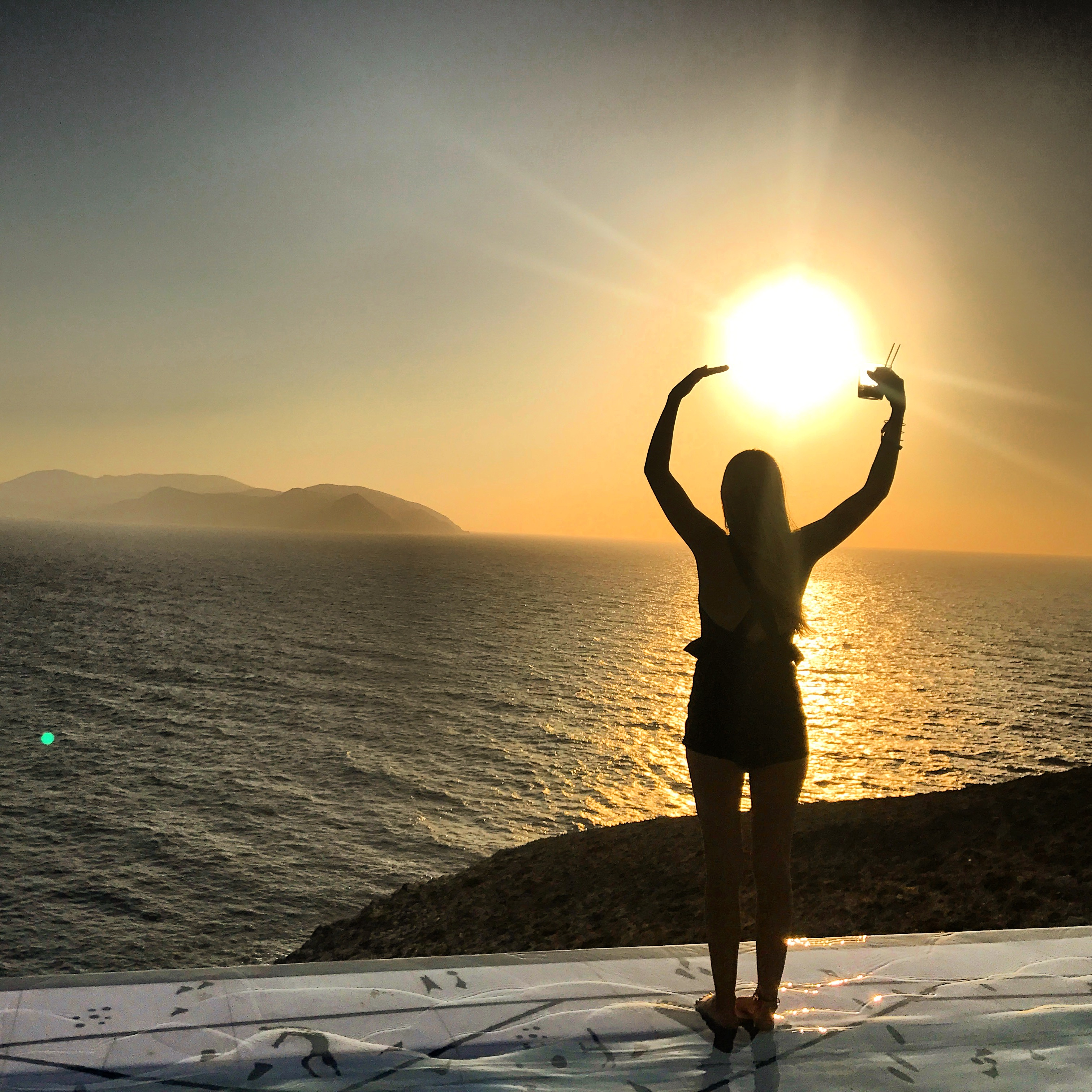 Girl sillohouetted against the sunset standing on top of an infinity pool in Ios, Greece