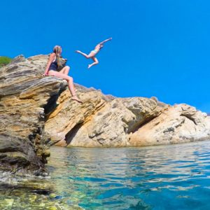 One girl jumping off a cliff into the ocean while another girl watches from the side line in Ios, Greece