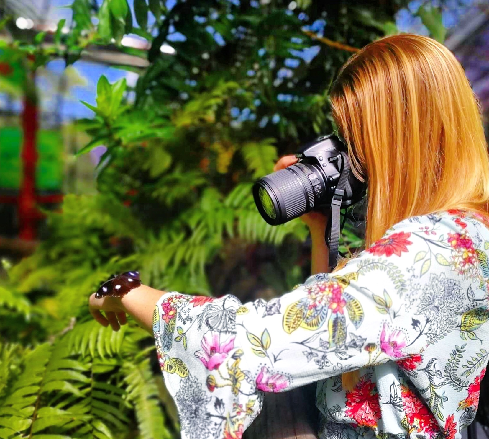 Girl taking a photo of a butterfly resting on her hand