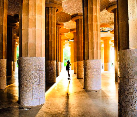 Girl standing in sunlight in columns at Park Guell