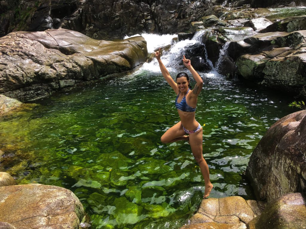 Girl about to jump into green rock pool in Behana Gorge in Cairns