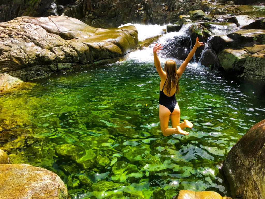 Girl jumping into green rock pool