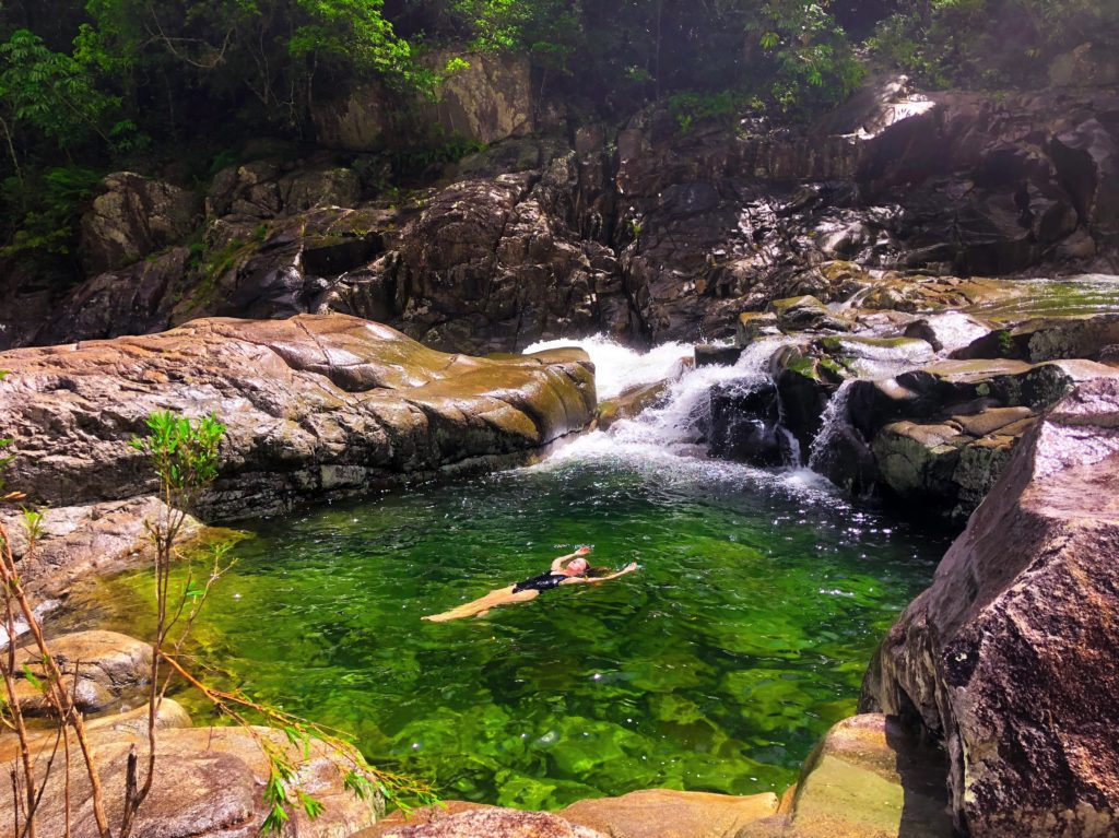 Girl floating in clear green rock pool in Behana Gorge in Cairns