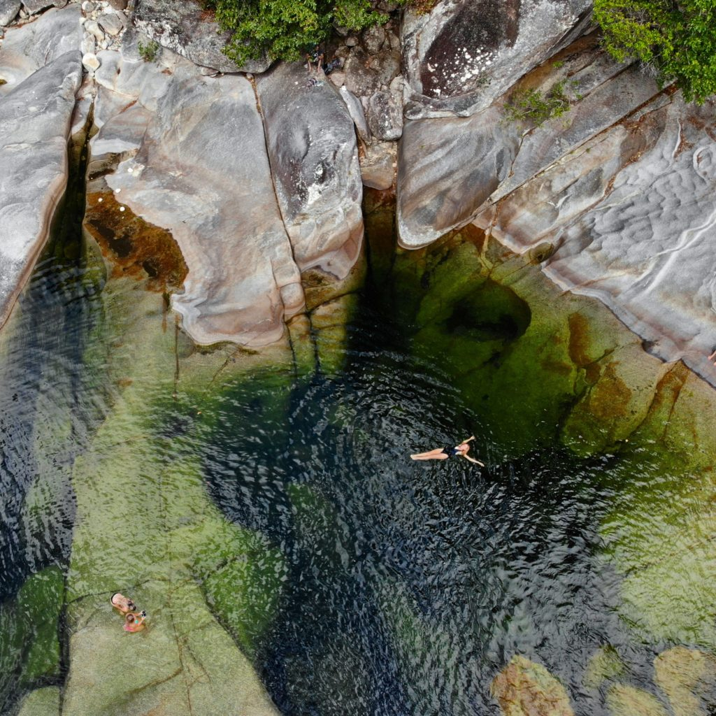 Girl floating in large green deep water hole in Behana Gorge in Cairns