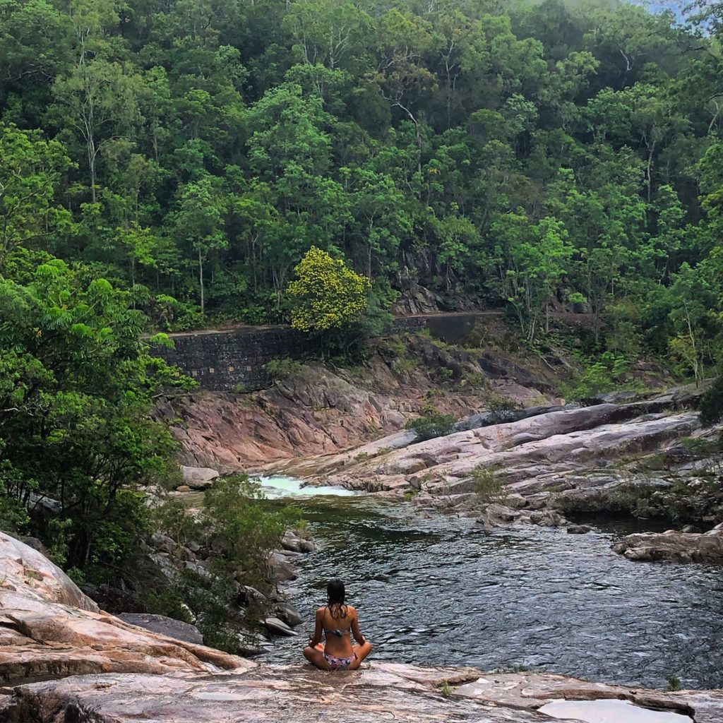 Girl sitting meditating in front of large water hole in the rainforest