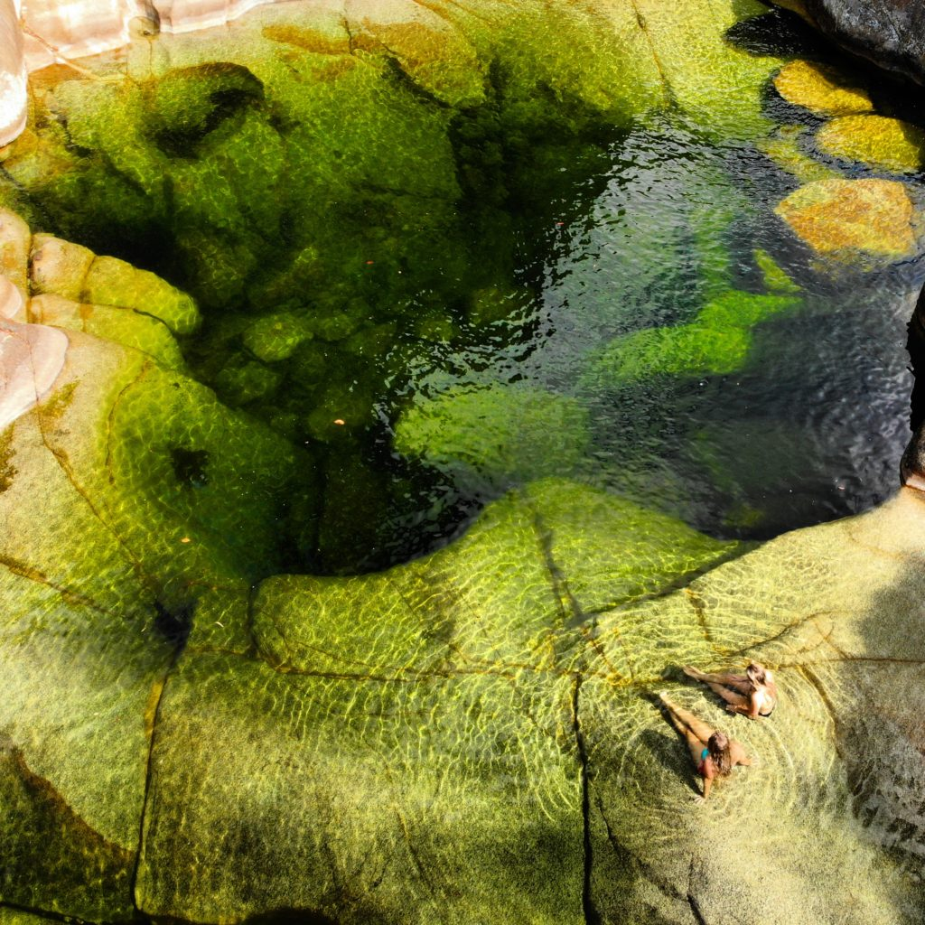 Two girls sitting next to very large green rock pool