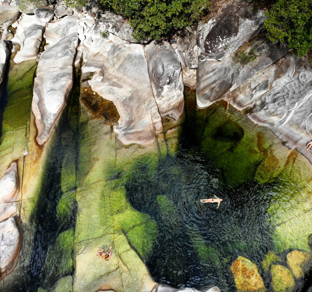 girl floating in dark green rock pool