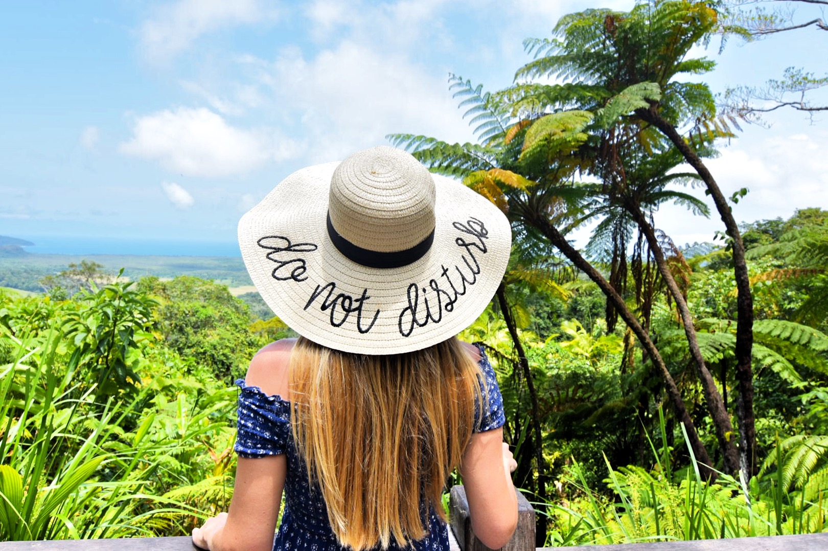 Girl standing in front of rainforest lookout with sunhat that says Do Not Disturb