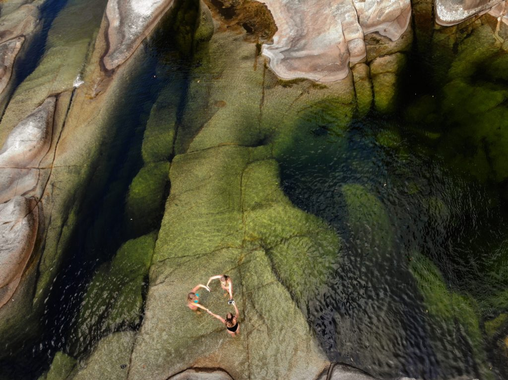 Three girls making love heart with their hands at a very large clear green rock pool - taken by a drone