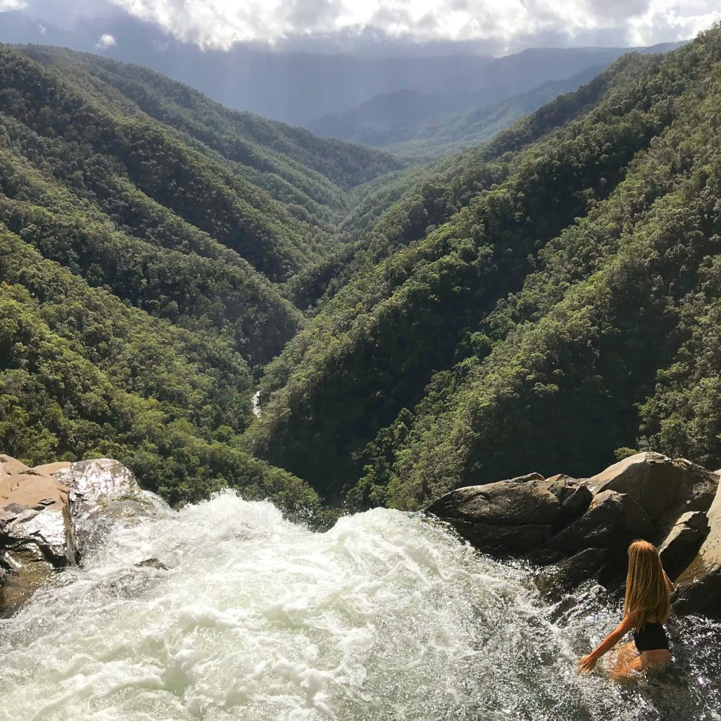 girl sitting on the edge of the top of Windin Falls waterfall looking out over valley