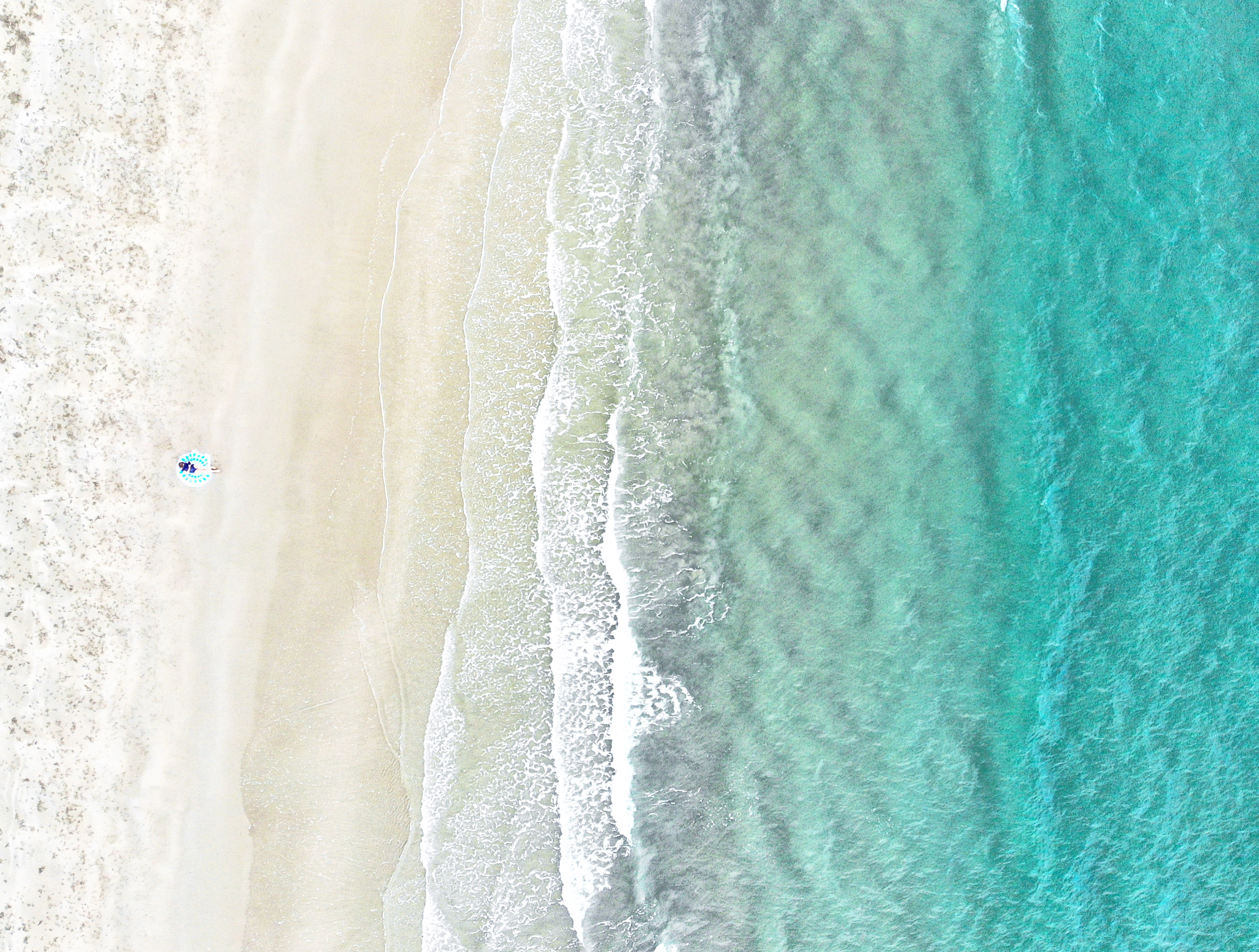 Girl sitting on the sand in front of the ocean taken from above