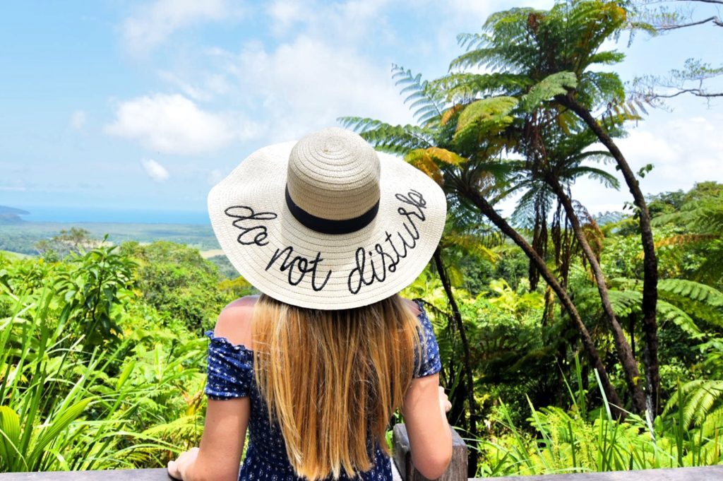 "Girl standing with a sunhat that says ""Do not Disturb"""