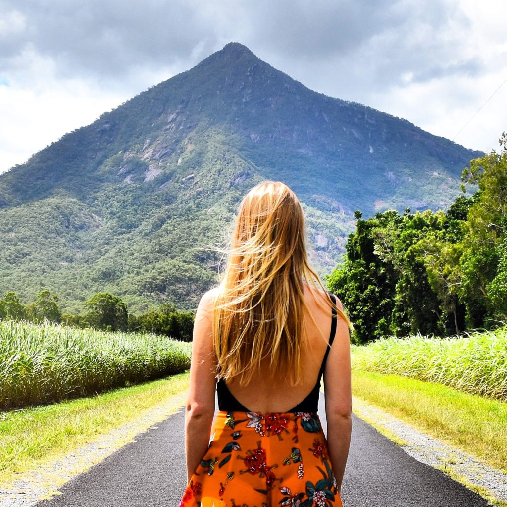 Girl standing on road looking up at pyramid shaped mountain