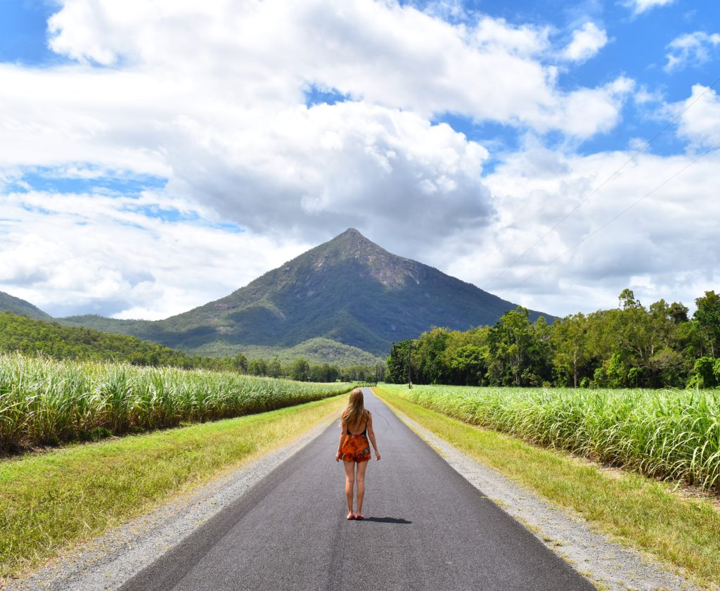 Girl standing on road looking up at Walsh's Pyramid in Cairns