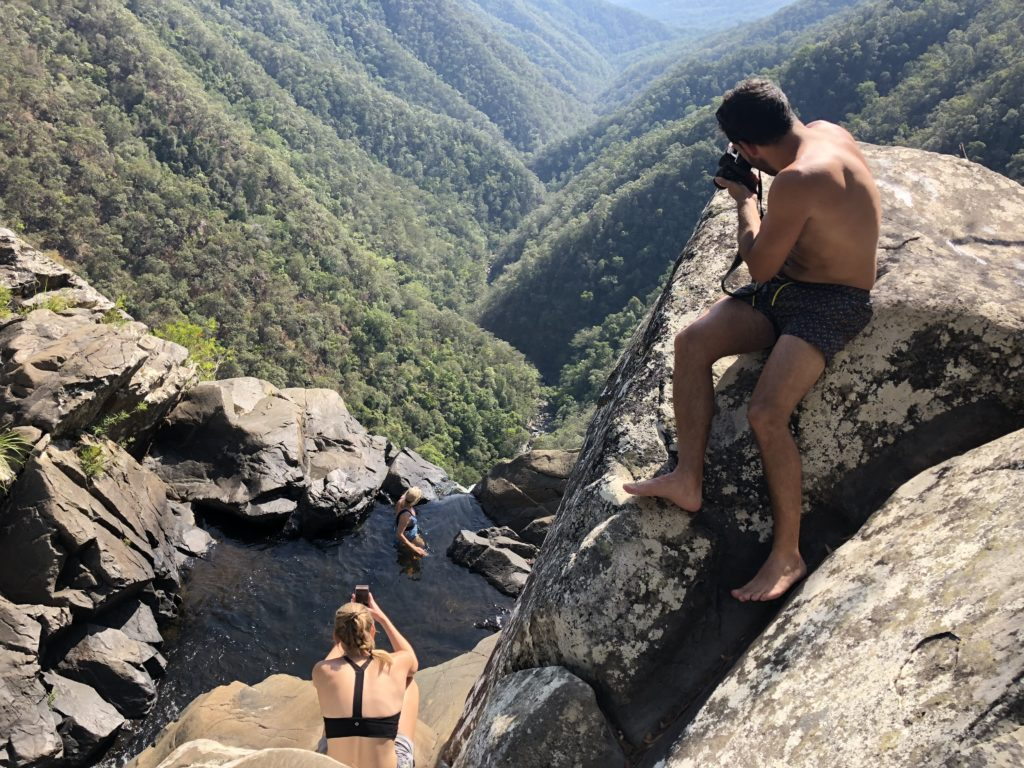 three people taking photos of each other at the top of Windin Falls