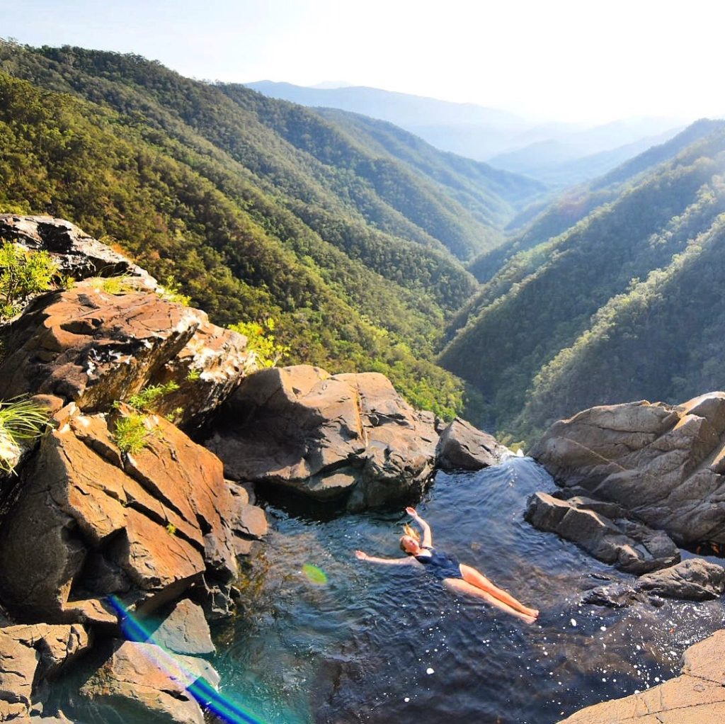 Girl floating at the top of Windin Falls waterfall overlooking the valley below