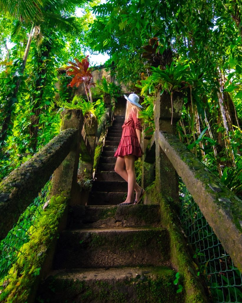 Girl standing on grand staircase in rainforest at Paronella Park