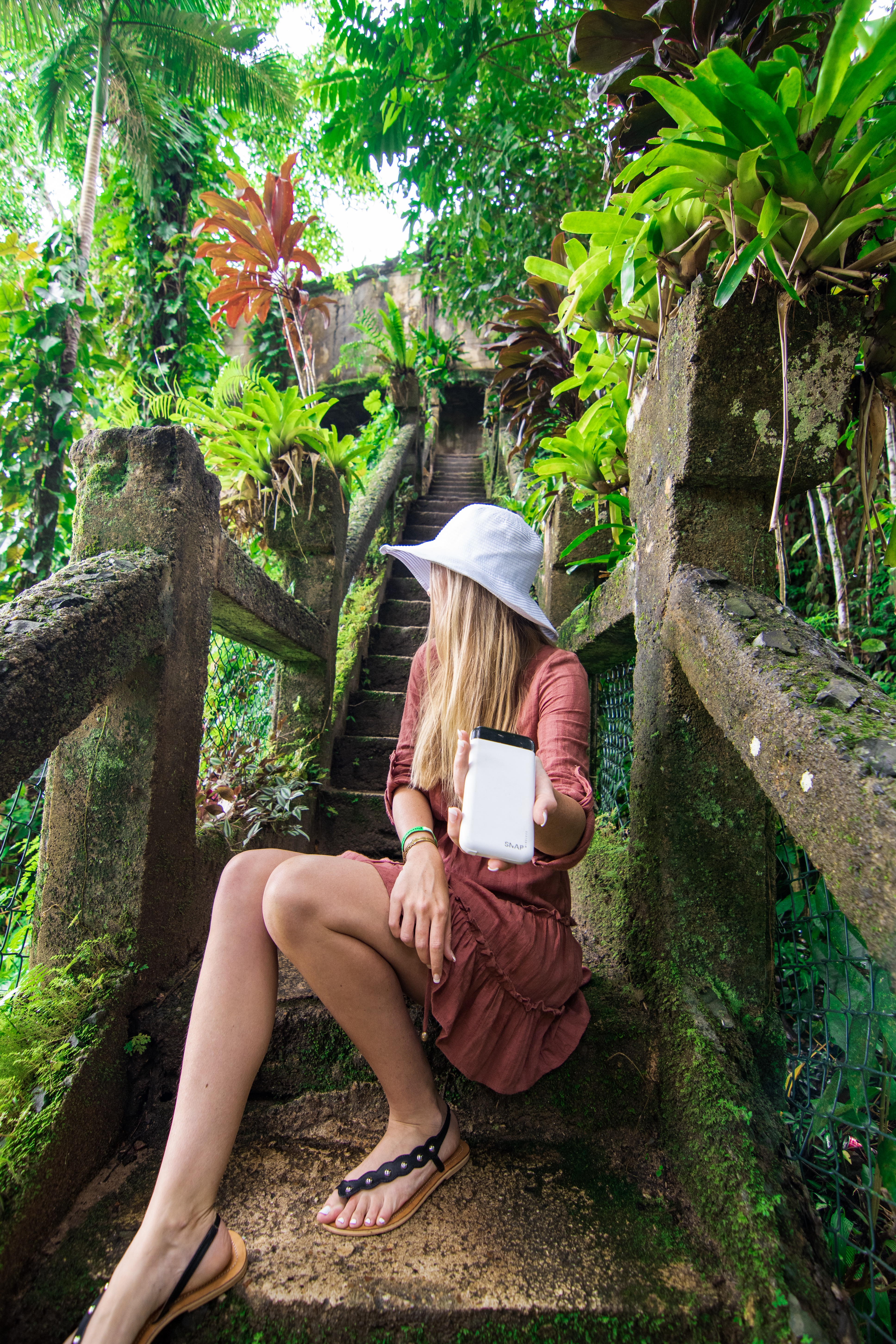 Girl holding Snap Wireless battery pack charger sitting on staircase in the rainforest at Paronella Park