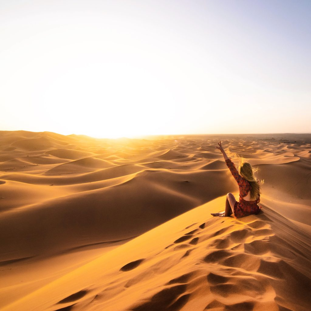 Girl sitting on a big Sahara Desert sand dune at sunset