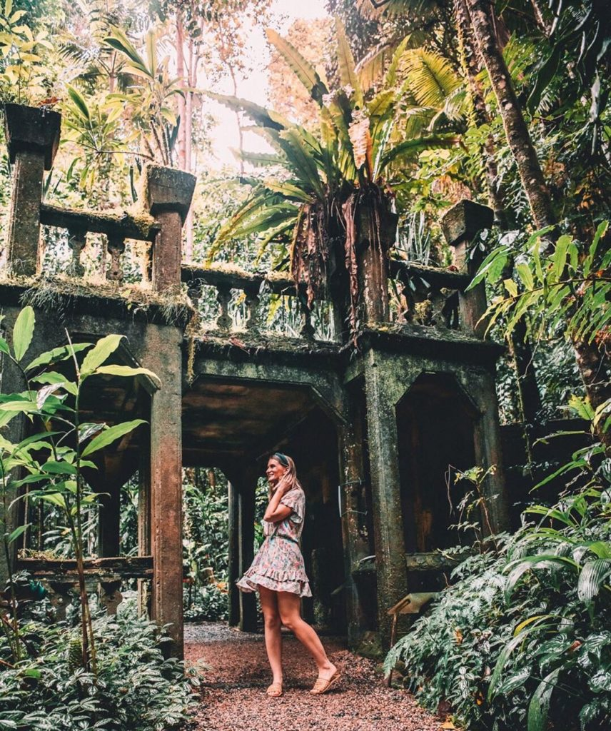 Girl standing in front of castle ruins at Paronella Park