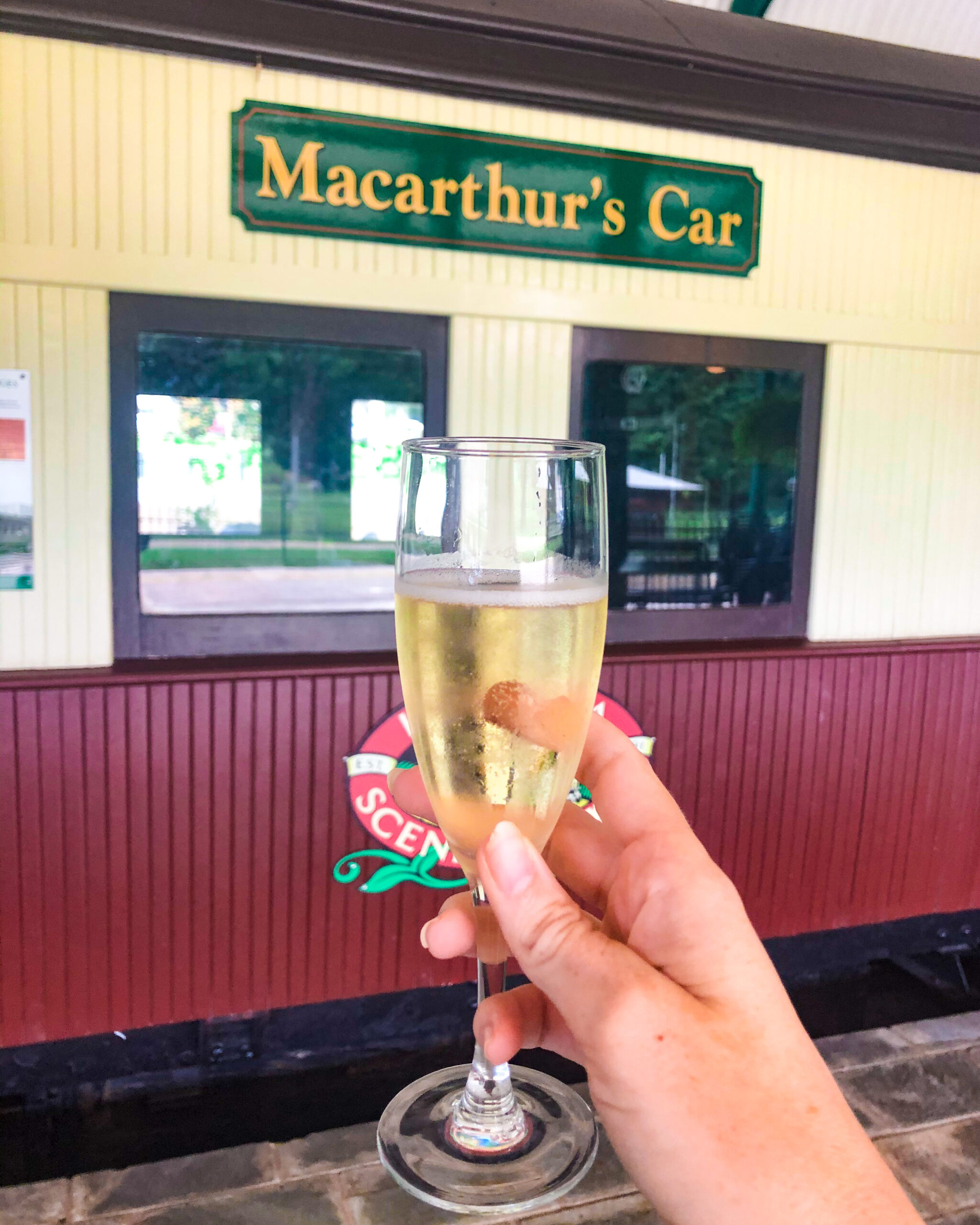 Champagne held in front of railway carriage at High Tea Trolley