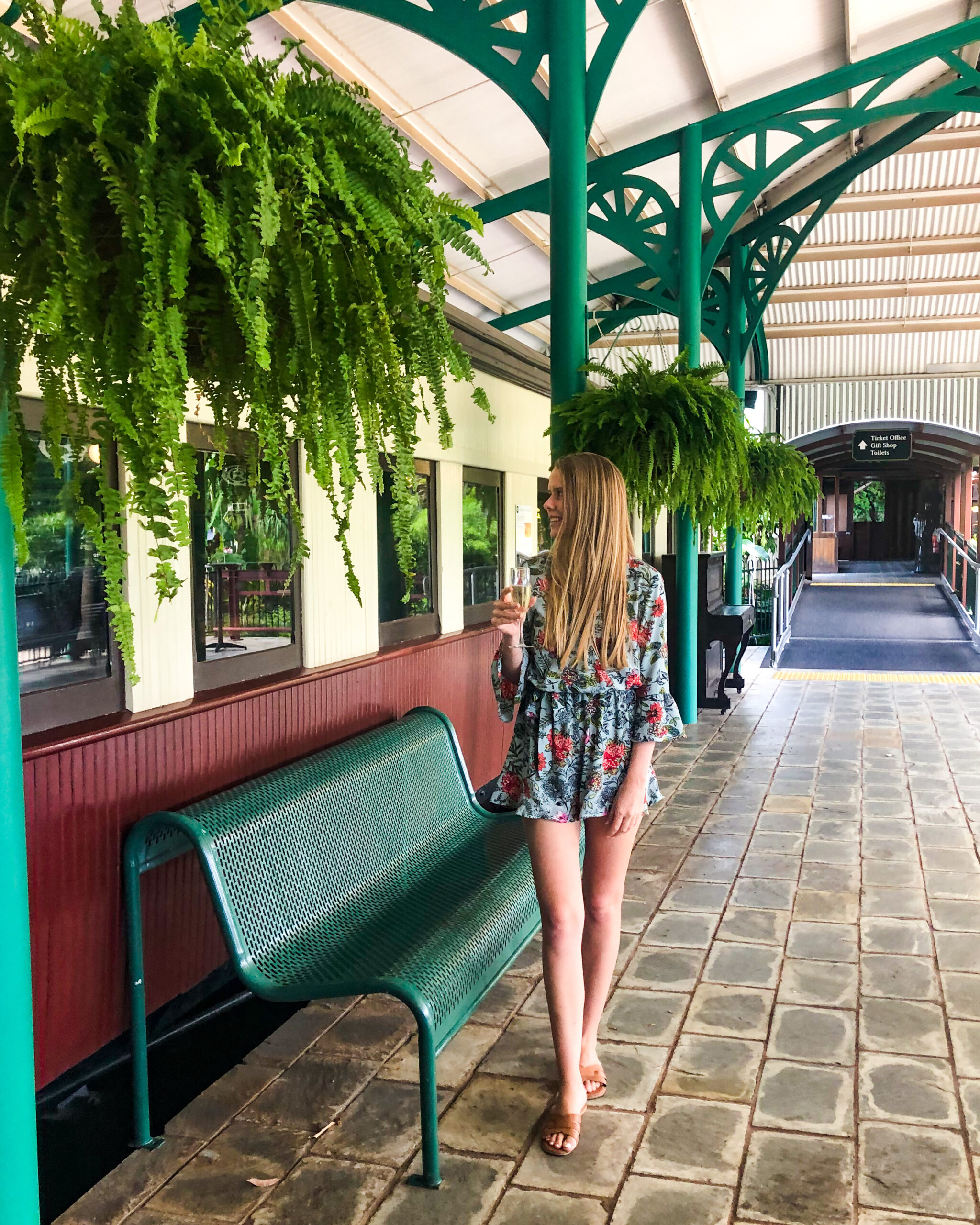 Girl standing holding champagne glass in front of train carriage at train station at the High Tea Trolley